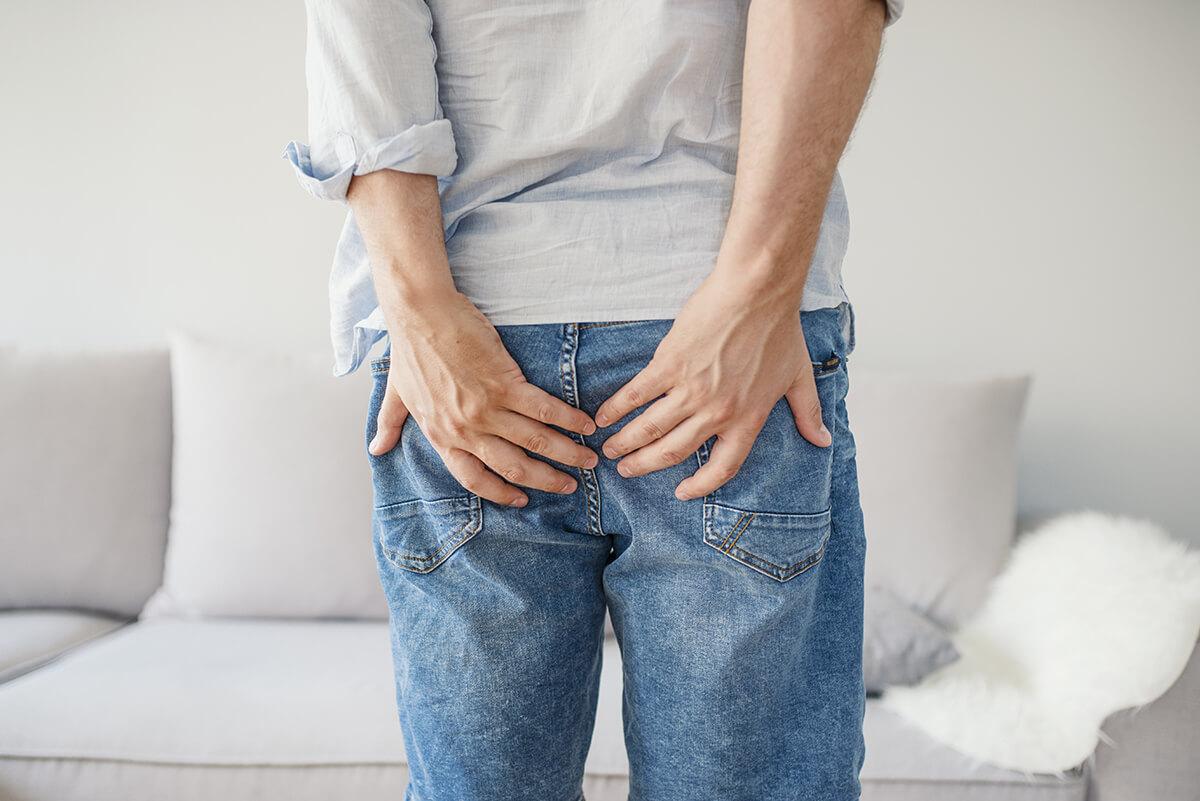 Mężczyzna trzymający się za pośladki - czym jest błona śluzowa odbytu