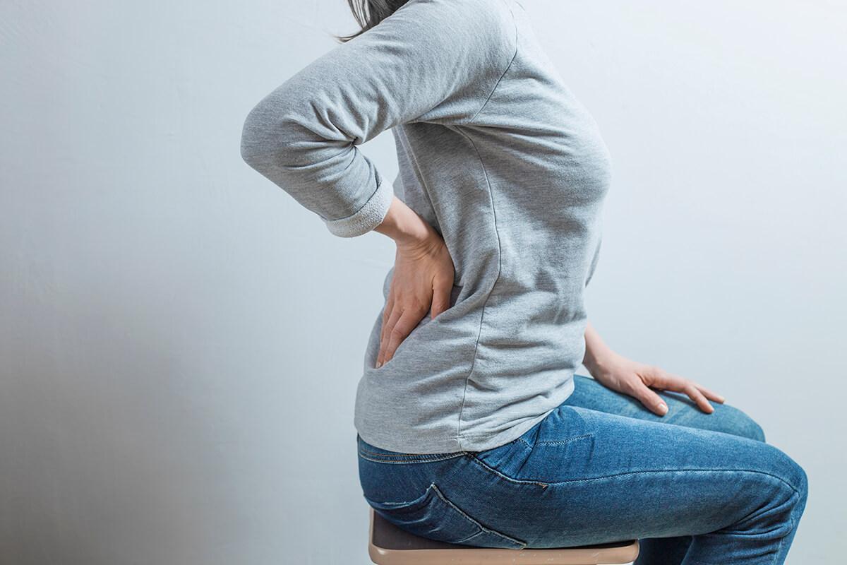 Kobieta trzyma dłoń na nerkach - po co należy zrobić badanie moczu