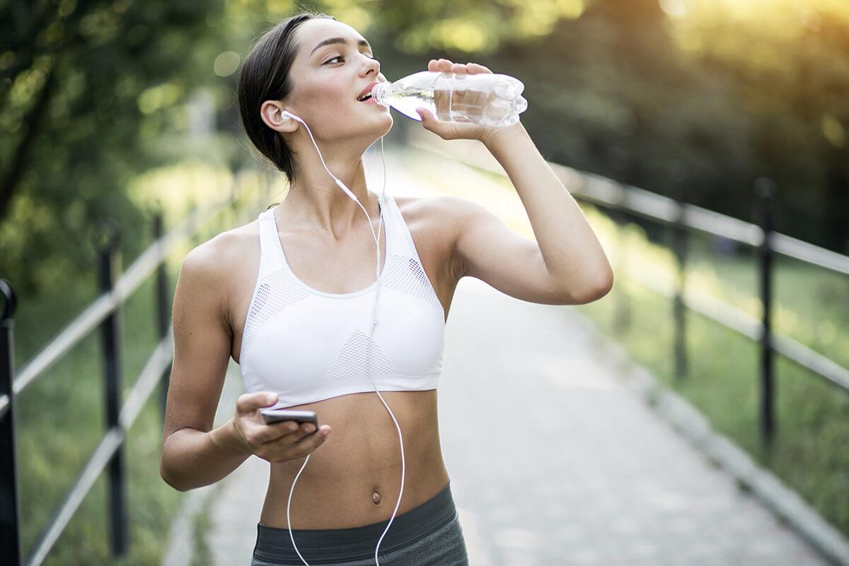 Kobieta biega, pije wodę - Plastyka piersi - co z aktywnością fizyczną po zabiegu