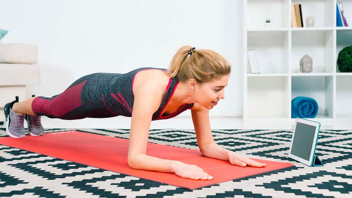 Kobieta ćwiczy w domu - jak nie przytyć podczas kwarantanny