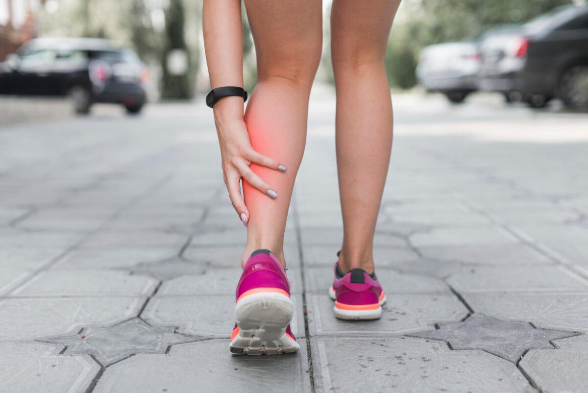 Kobieta trzyma się za bolącą łydkę - Najczęstsze schorzenia narządu ruchu