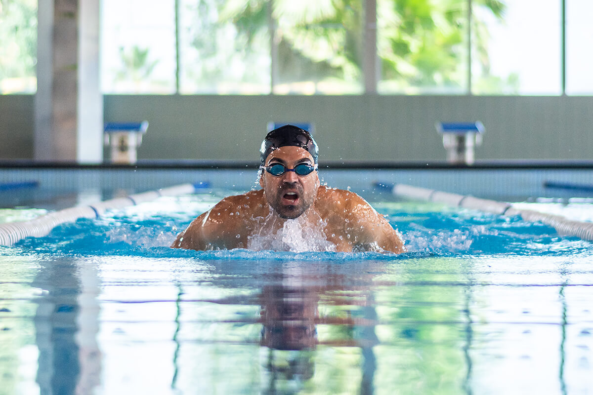 Mężczyzna w basenie - powody dla których warto pływać
