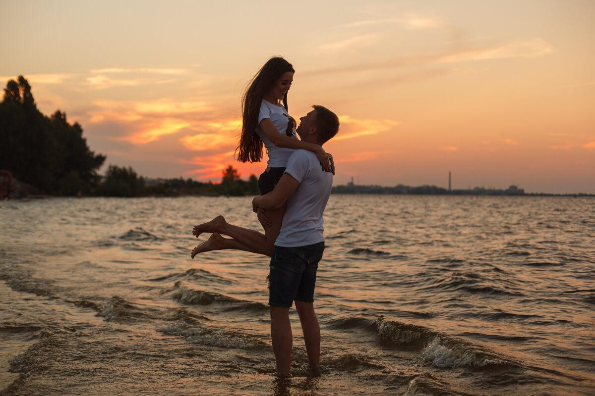 Dziewczyna w objęciach chłopaka stojącego w morzu. Problemy ginekologiczne