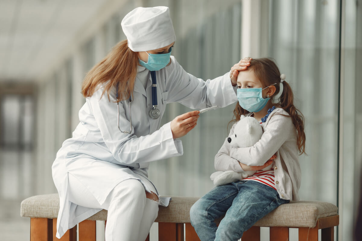 Lekarka mierzy temperaturę dziewczynce. Prywatna służba zdrowia podczas pandemii COVID-19