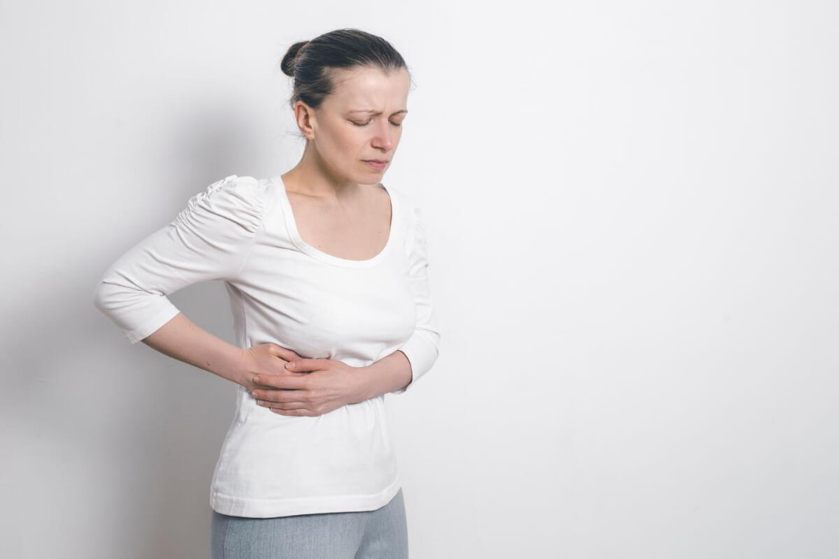 Kobieta trzyma się za prawy bok. Samoleczenie wątroby - na czym polega i jak je wspierać?