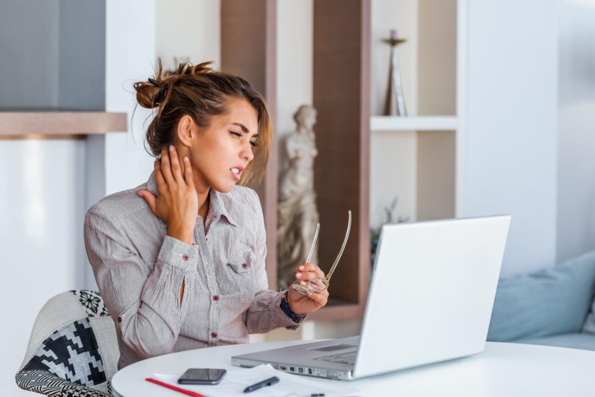 Kobieta przed laptopem dotyka bolącej szyi. Siedzący tryb życia - to nie tylko problemy z krążeniem