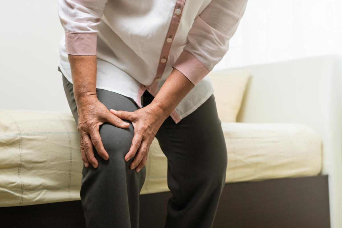 Starsza kobieta trzymająca się za kolano. Strzelające stawy - kiedy udać się do lekarza